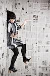 Jeune femme collé au mur recouvert de journaux, studio shot