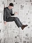 Jeune homme collé au mur recouvert de journaux, studio shot