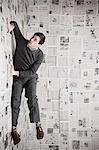 Jeune homme collé au mur recouvert de journaux tentant de s'échapper, studio shot