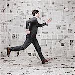 Jeune homme exécuté devant le mur recouvert de journaux