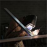 USA, Utah, Orem, man soldering metal in workshop