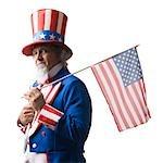 Homme en costume de l'oncle Sam, tenant le drapeau américain, studio shot