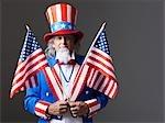 Homme en costume de l'oncle Sam tenant des drapeaux américains, studio shot