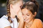 Two girls outside whispering