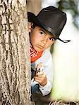 Boy in cowboy costume with toy gun