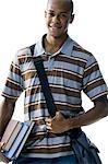 Teenage boy with bookbag and books
