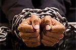 Businessman's hands bound in chains