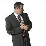 Businessman putting money into his jacket