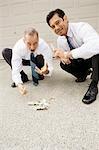 Two businessmen gambling on a driveway