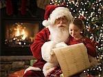 Père Noël avec une petite fille sur ses genoux