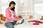 Femme enceinte avec les vêtements de bébé
