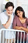 Couple marié, se penchant sur le lit pour bébé
