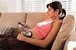 Femme enceinte au repos avec un casque sur l'abdomen