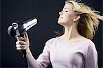 Coup de femme séchage des cheveux blonds avec des yeux fermés