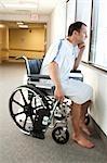 Man in hospital gown sitting in wheelchair looking through window