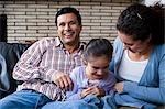 Homme et femme chatouiller la fille sur le canapé
