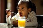 Junges Mädchen essen Getreide und Glas Orangensaft