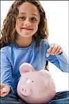 Young girl depositing money in piggy bank