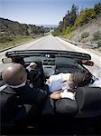 Vue arrière d'un couple de jeunes mariés dans une voiture décapotable
