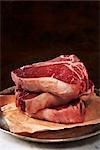 Trois crus biftecks d'aloyau sur du papier de boucherie