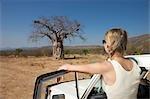 Young woman next to motor vehicle looking at Baobab tree, Epupa Falls area, Kaokoland, Namibia