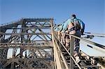 Un groupe d'alpinistes font leur chemin vers le haut des poutres d'acier du pont histoire de Brisbane. La montée d'aventure pont histoire commencée en 2005 et est l'un de seulement quatre de ces expériences dans le monde.