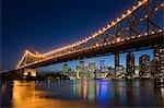 Toits de la ville de Brisbane au crépuscule, avec le Story Bridge illuminé au-dessus de la rivière Brisbane.