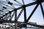 Un groupe d'alpinistes mise à l'échelle de l'arc de la suspension du Sydney Harbour Bridge est éclipsée par des poutres d'acier de la structure au-dessus du port