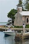 Surplombé par la chapelle rustique de l'île, un bateau pénètre dans le havre de Little Whale Cay