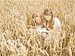 Girls reading in wheat field