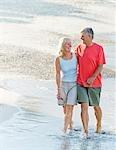 Senior couple walk along the beach