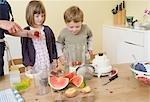 garçon et fille à préparer des smoothies aux fruits