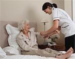 Nurse rolling up elderly woman's sleeve