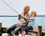 boy fishing with grandfather at lake