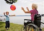 boy playing ball with senior woman