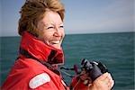 Femme avec des jumelles de l'océan