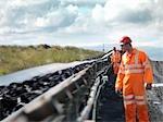 Kohle-Arbeiter untersuchen die Transportband