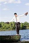 businessman balancing on rowboat