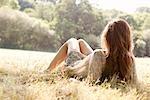 Woman lying in countryside field