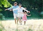 Family fun walking in country field