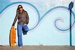 Frau auf dem Boardwalk posiert mit ihrem Skateboard, Santa Cruz, Kalifornien, USA