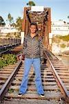 Frau auf Eisenbahnschienen posiert mit ihrem Skateboard, Santa Cruz, Kalifornien, USA