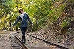Femme marche le long d'une ancienne voie ferrée dans une forêt de séquoias, près de Santa Cruz, Californie, USA