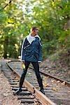 Femme sur une ancienne voie ferrée dans une forêt de séquoias, près de Santa Cruz, Californie, USA