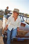 Femme assise sur le capot d'une voiture Vintage à la plage, Santa Cruz, Californie, USA