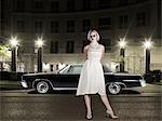 Portrait de femme glamour, debout devant un Condo de luxe et une 1964 Chevrolet Imperial LeBaron