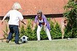 grand-mère et enfants jouant au football