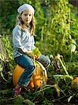 Jeune fille assise sur une citrouille