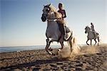 Two women riding horses on beach
