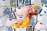 Wasting money, conceptual image. Flames engulfing Euro notes.